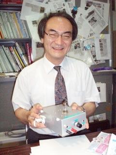 手製の真空管アンプを見せる平間教授