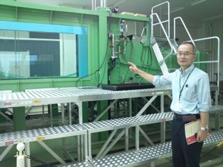 実験用水槽を説明する佐藤先生
