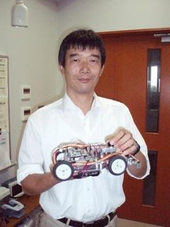 授業で使うマイコンカーを手にする藤木先生